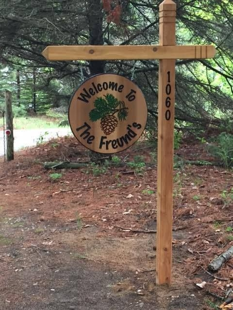 hanging family sign with 4x4 posts carved ends and address Cabin Sign Ideas