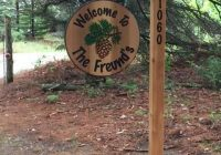 hanging family sign with 4×4 posts carved ends and address Cabin Sign Ideas